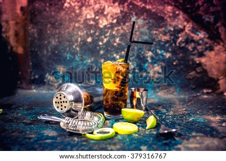 Alcoholic cocktail beverage, cuba libre drink with garnish and metal background - stock photo