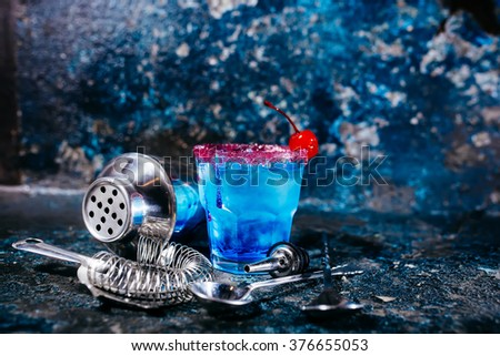 alcoholic cocktail drink with blue curacao and cherry served at bar - stock photo