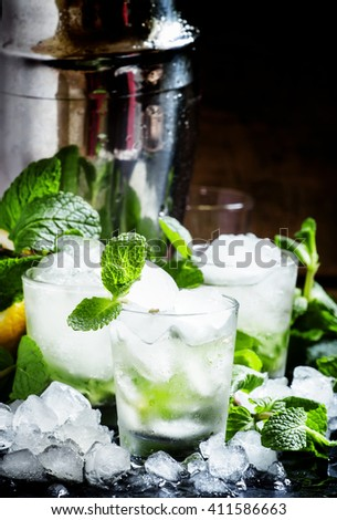 Alcoholic cocktail vodka smash with vodka, sugar syrup, soda, lime, mint and crushed ice, black background, selective focus - stock photo