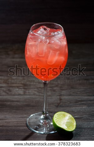 Alcoholic cocktail with lime and drunk on a dark background - stock photo