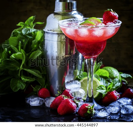 Alcoholic cocktail with strawberry, lime and ice, black background, selective focus - stock photo