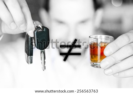 Alcoholic drink and car keys in hands with inequality opposition symbol - do not drink and drive concept - stock photo