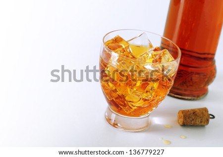 Alcoholic drink in a glass with ice cubes and a bottle and cork over white background - stock photo