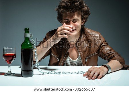 Alcoholic drunk man drinking wine, feeling depressed, falling into addiction problem / photo of youth addicted to alcohol, alcoholism concept, social problem - stock photo