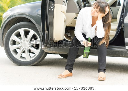 Alcoholic female enjoying a lonely drink sitting in the open door of her parked car with a bottle of booze staring despondently into the distance - stock photo