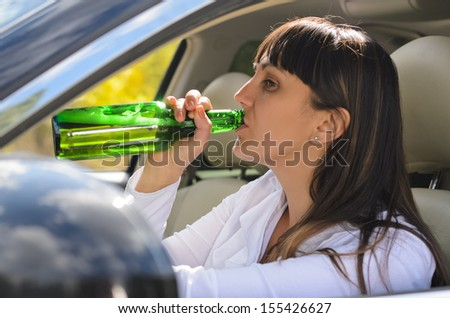 Alcoholic woman drinking and driving raising the bottle to her lips to take a swig as she steers the car, view through the side window - stock photo