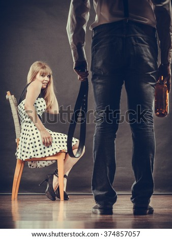 Alcoholism and violence problem. Man alcoholic holding bottle beating his scared wife with belt. Woman is victim of domestic abuse. - stock photo