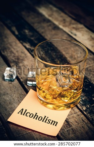 alcoholism with label on paper note. Glass of scotch whiskey  - stock photo