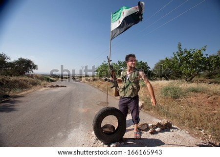 ALEPPO COUNTRYSIDE, SYRIA - JUNE 19  2012.   Unidentified rebel of the Free Syrian Army stands on guard on the road to Aleppo, on June 19, 2012. - stock photo