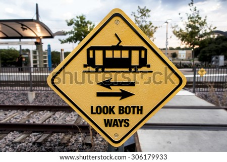 Alert sign warning train commuters to look down the tracks before crossing - stock photo