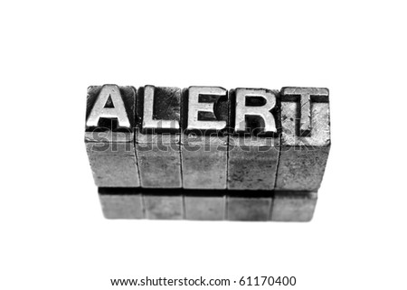 ALERT written in metallic letters on a white background - stock photo