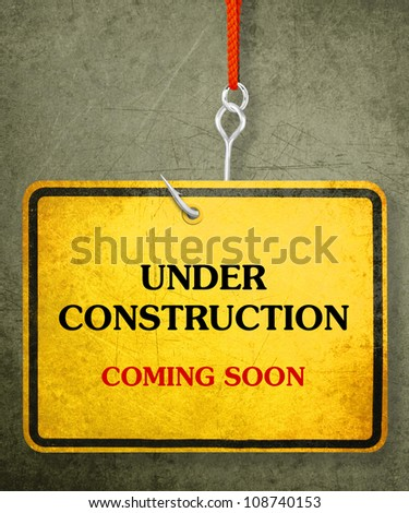 Alert yellow sign hanging by fishhook, conceptual image for under construction and coming soon - stock photo