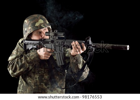 Alerted soldier keeping a smoking gun. Isolated - stock photo