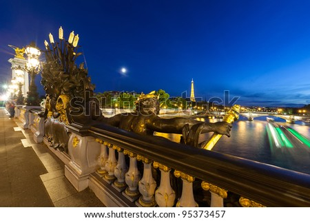 Alexander III bridge at night and boat on the Seine looking towards Eiffel Tower - stock photo