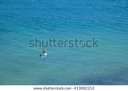 ALGARVE, PORTUGAL - April 24, 2016: Woman practicing Paddleboard in Albandeira beach in Lagoa, a popular beach among tourists during summer season . Travel and vacation destinations. - stock photo