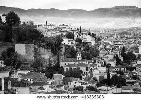 Alhambra palace located in Granada, Andalusia, Spain with aerial view at the city and mountains in the morning. It is a UNESCO World Heritage Site and a major touristic attraction. Black and white - stock photo