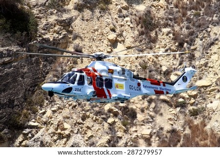 ALICANTE COAST, SPAIN - JUNE 14: Helicopter of the Spanish  Maritime Rescue Team finding injured over Cabo La Nao beach, on june 14, 2015 in Alicante coast. - stock photo
