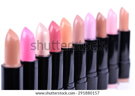 Align lipsticks different colours, closeup on white