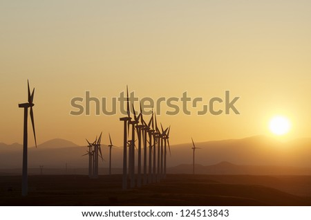 aligned windmills for renowable electric production at sunset, Pozuelo de Aragon, Zaragoza, Aragon, Spain - stock photo