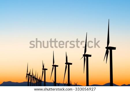 aligned windmills for renowable electric production at sunset, Pozuelo de Aragon, Zaragoza, Aragon, Spain - stock photo