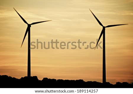aligned windmills for renowable electric production at sunset, Zaragoza province, Spain - stock photo