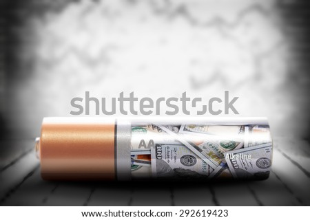 Alkaline battery with dollars inside on grunge background - stock photo