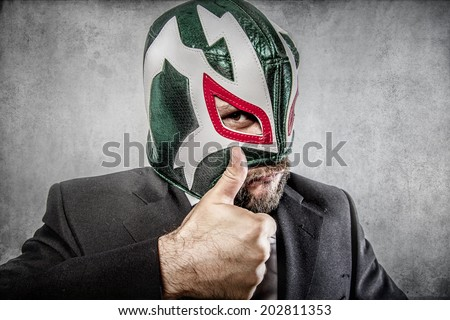 all it is ok, aggressive executive suit and tie, Mexican wrestler mask - stock photo
