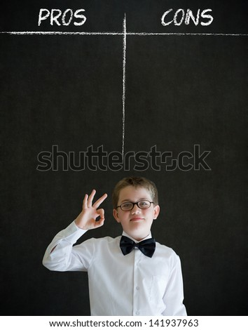 All ok or okay sign boy dressed up as business man with chalk pros and cons decision list on blackboard background - stock photo