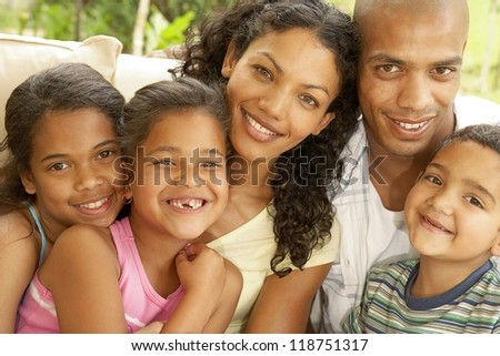 All smiles from a happy fimily as the kids crowd around mom and dad. - stock photo