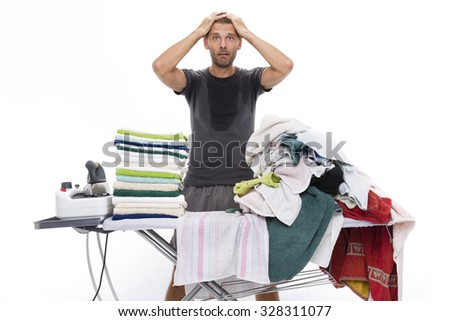 all sweaty and desperate man puts his hands through his hair because he has to stretch a stack of towels placed on a ironing board - stock photo