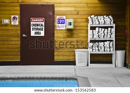 All swimming pools take maintenance with chemicals. The door leads to the chemical storage area. Emergency signs are on the wall. - stock photo