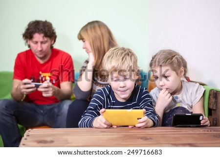 All the family sitting fascinated phones and smartphones - stock photo