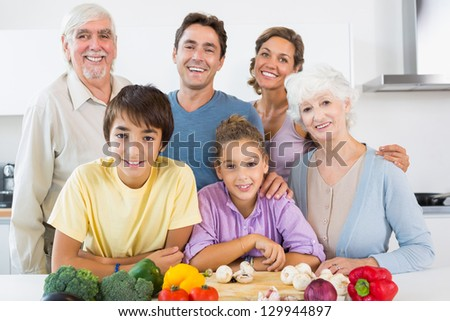 All the family smiling in kitchen in front of chopping board with vegetables - stock photo