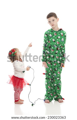 All tied up!  Adorable toddler laughing at her big brother who is all tied up in Christmas lights.  Isolated on white.  - stock photo
