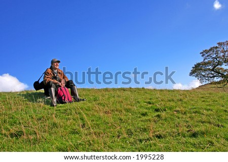 All Tucker out after a Hike in English Countryside man sits on Rock to enjoy the View - stock photo