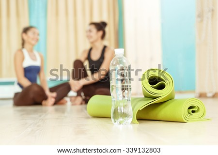 All you need for yoga. Selective focus on a yoga mat and a bottle of water two female friends talking on the background in yoga studio - stock photo