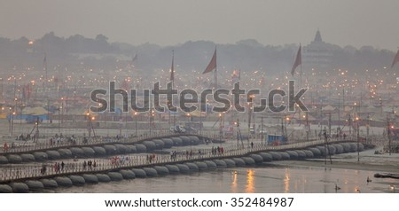 ALLAHABAD, INDIA - FEBRUARY 06, 2013: Thousands of Hindu devotees crossing the pontoon bridges over the Ganges River at Maha Kumbh Mela festival in Allahabad, India. - stock photo