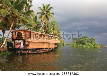 ALLEPPEY, INDIA -APR 16 : A house boat  transports tourists around the backwaters on April 16, 2010 in Alleppey, India. House boat cruise is the top attraction of the inbound tourism in Kerala. - stock photo