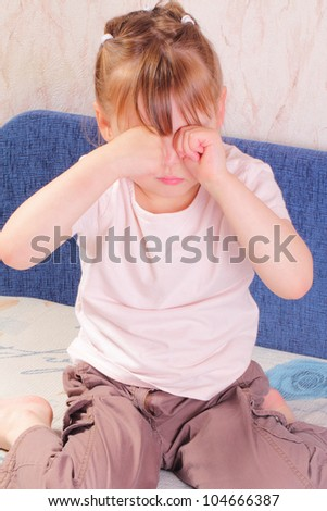 Allergic little girl scratching her eyes - stock photo