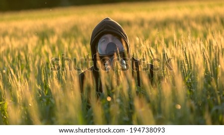 Allergic man with gasmask at the field - stock photo
