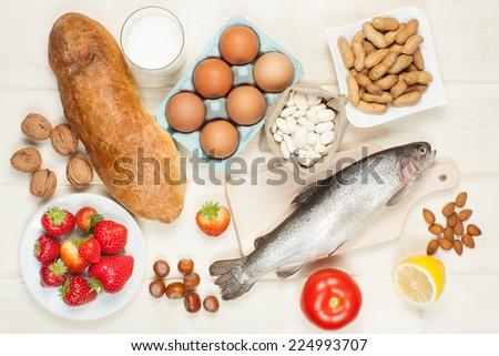 Allergy food concept - bread, milk, fruits, nuts, eggs and beans on wooden table - stock photo