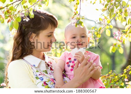 Allergy. Mother and baby blowing nose outdoors - stock photo