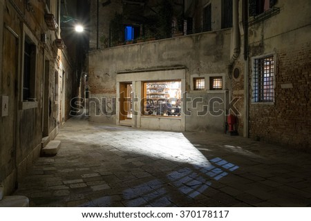 Alley way at night in Venice with geometric white and blue reflections on the cobblestone - stock photo