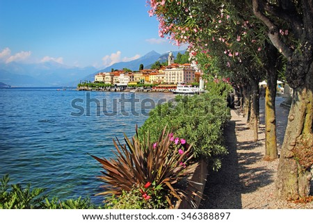 Alley with blossoming trees and flowers along Como lake with view of old Bellagio town in summertime, Italy. - stock photo