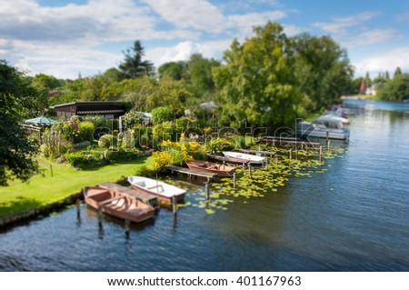 Allotment garden on the banks of a canal, very idyllic, green, flowers, boats. Sunshine. Miniature. - stock photo