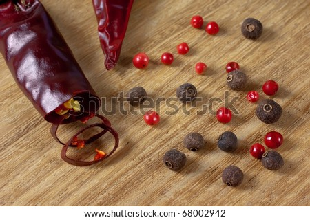 Allspice, Rose and Red hot pepper on wooden background close up - stock photo