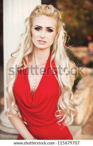 alluring blond relaxing in luxury interior. Stylish rich slim girl in sexy red dress with healthy glossy curly hair at hotel villa apartment. Fashion glamorous shot at vacation resort autumn - stock photo