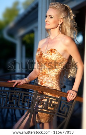 alluring blond relaxing in luxury villa. Stylish rich slim girl in sexy golden dress with healthy glossy curly hair outdoor. Fashion glamorous shot autumn - stock photo