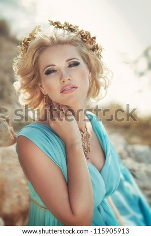 alluring blond woman in Greek goddess style with golden jewelery in luxury dress on sunset near ancient ruins. stylish romantic girl in blue silk outdoor. romantic concept. Amazing Nymph. - stock photo