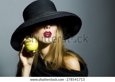 Alluring blonde girl in retro black hat with bright make up holding fresh green apple standing on gray background copyspace, horizontal picture - stock photo